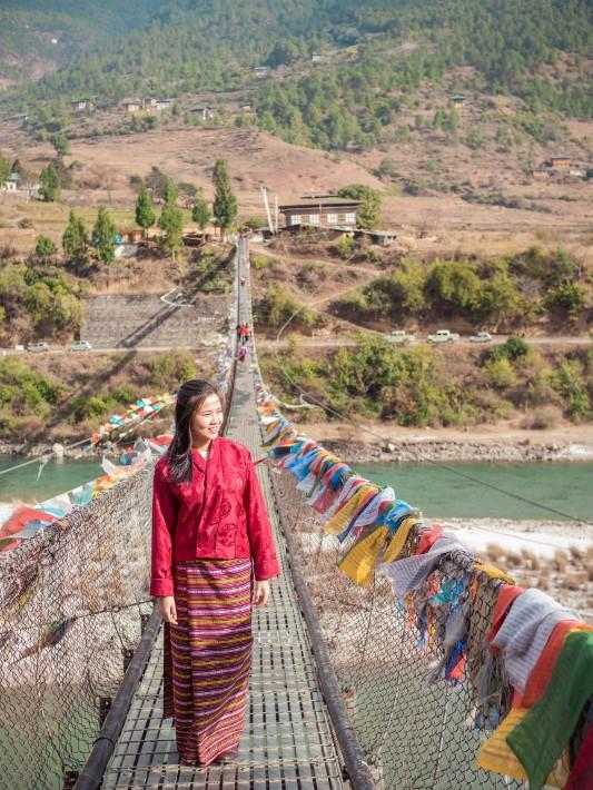 girl in traditional costume, bridge, punakha, bhutan