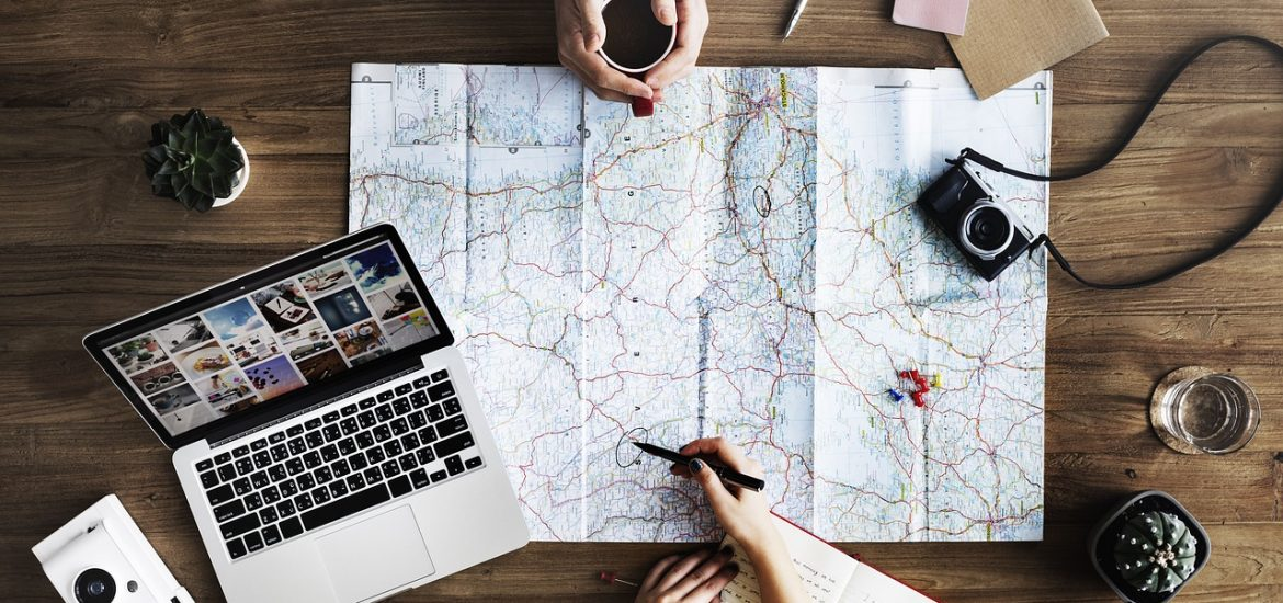 laptop map flatlay travel help career